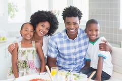 Famille heureuse s'asseyant au dîner ensemble Images stock