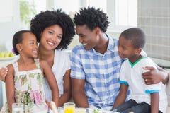 Famille heureuse s'asseyant au dîner ensemble Photographie stock libre de droits