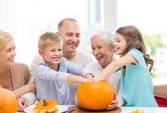 Famille heureuse s'asseyant avec des potirons à la maison Images libres de droits