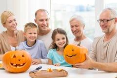 Famille heureuse s'asseyant avec des potirons à la maison Image libre de droits
