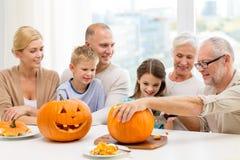 Famille heureuse s'asseyant avec des potirons à la maison Photos libres de droits
