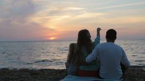 Famille heureuse s'asseyant dans le coucher du soleil près de la mer dedans clips vidéos