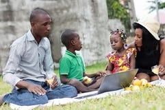 Famille heureuse s'asseyant dans le jardin et regardant ensemble sur un recouvrement images libres de droits