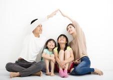 Famille heureuse s'asseyant ensemble et faisant le signe à la maison Image libre de droits