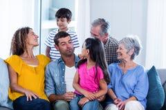 Famille heureuse s'asseyant ensemble sur le sofa à la maison Image libre de droits