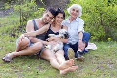 Famille heureuse s'asseyant et souriant en parc Photos libres de droits