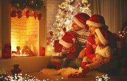 Famille heureuse s'asseyant par la cheminée le réveillon de Noël Photos stock