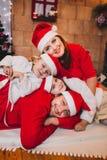 Famille heureuse s'asseyant près de l'arbre de Noël En rouge Photographie stock libre de droits