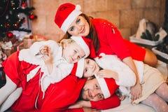 Famille heureuse s'asseyant près de l'arbre de Noël En rouge Photo libre de droits