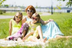 Famille heureuse s'asseyant sur l'herbe Photos stock