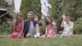 Famille heureuse s'asseyant sur l'herbe dans le jardin ensemble Mère, père, fils, et fille regardant dans la caméra clips vidéos