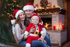 Famille heureuse s'asseyant sur le divan à la maison devant la cheminée dans la pièce de fête de Noël Photographie stock libre de droits