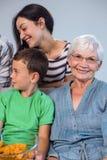 Famille heureuse s'asseyant sur le sofa Photographie stock