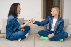 Famille heureuse s'asseyant sur le sofa et à l'aide du comprimé numérique à la maison Image libre de droits