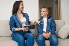 Famille heureuse s'asseyant sur le sofa et à l'aide du comprimé numérique à la maison Image stock