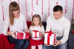 Famille heureuse s'asseyant sur le sofa et les cadeaux s'ouvrants de Noël Images libres de droits