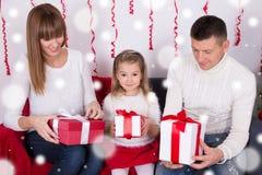 Famille heureuse s'asseyant sur le sofa et les cadeaux s'ouvrants de Noël Image libre de droits