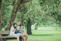 Famille heureuse s'asseyant sur un banc en parc et jouant avec Han Photos libres de droits