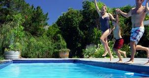 Famille heureuse sautant dans la piscine banque de vidéos