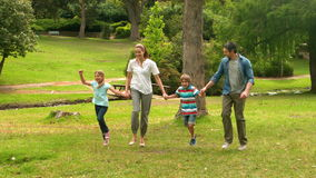 Famille heureuse sautant en parc banque de vidéos