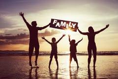 Famille heureuse sautant sur la plage au temps de coucher du soleil photographie stock