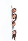 Famille heureuse se cachant derrière le panneau d'affichage Images libres de droits