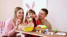 Famille heureuse se composant de la maman, du papa et de la fille silencieusement confer et puis soudainement et avec une exposit banque de vidéos