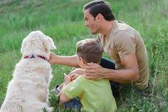 Famille heureuse se reposant avec l'animal familier sur le pré Photographie stock libre de droits
