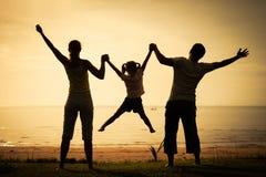 Famille heureuse se tenant sur la plage Photo stock