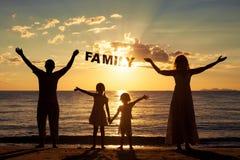 Famille heureuse se tenant sur la plage au temps de coucher du soleil Photo stock