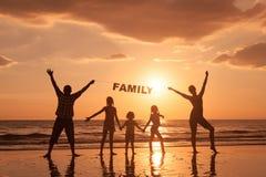 Famille heureuse se tenant sur la plage au temps de coucher du soleil Photo libre de droits