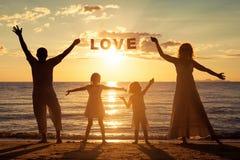 Famille heureuse se tenant sur la plage au temps de coucher du soleil Image stock