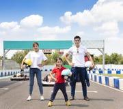 Famille heureuse se tenant sur la voie de course de kart d'aller photos libres de droits