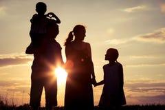Famille heureuse se tenant sur le champ au temps de coucher du soleil Photographie stock