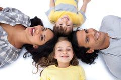 Famille heureuse se trouvant ensemble sur l'étage en cercle Image stock