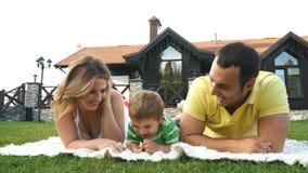 Famille heureuse se trouvant sur l'herbe en parc et rires clips vidéos