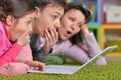 Famille heureuse se trouvant sur le plancher devant l'ordinateur portable images libres de droits