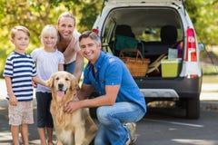 Famille heureuse souriant à l'appareil-photo avec leur chien photographie stock libre de droits
