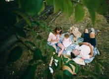 Famille heureuse sur la pelouse en parc Photo stock