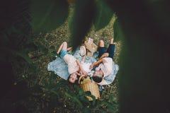 Famille heureuse sur la pelouse en parc Photos stock