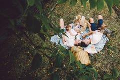 Famille heureuse sur la pelouse en parc Photographie stock