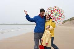 Famille heureuse sur la plage avec le parapluie images libres de droits