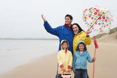 Famille heureuse sur la plage avec le parapluie photo stock