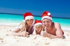 Famille heureuse sur la plage dans des chapeaux de Santa, Noël de célébration Images stock