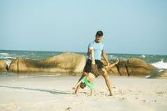 Famille heureuse sur la plage jouant, p?re avec la c?te de marche de fils, roches derri?re des vacances de prise de sourire images stock