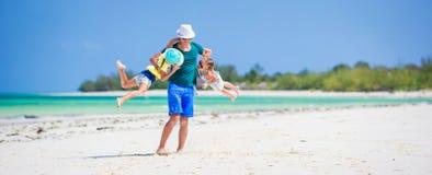 Famille heureuse sur la plage tropicale ayant l'amusement ensemble Photos stock