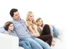 Famille heureuse sur le divan d'isolement Photo stock