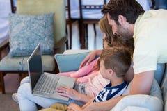 Famille heureuse sur le divan ensemble utilisant l'ordinateur portable Photos libres de droits