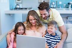 Famille heureuse sur le divan ensemble utilisant l'ordinateur portable Images stock