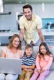 Famille heureuse sur le divan ensemble utilisant l'ordinateur portable Images libres de droits